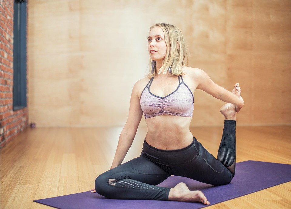 Blonde, fit woman in exercise top and yoga pants doing a yoga pose on a mat