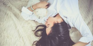 Beautiful woman lying on bed with her eyes closed and cuddling a puppy