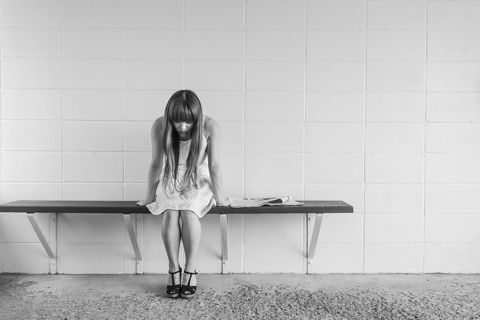 Woman with long hair in a white dress sitting on bench looking down and depressed